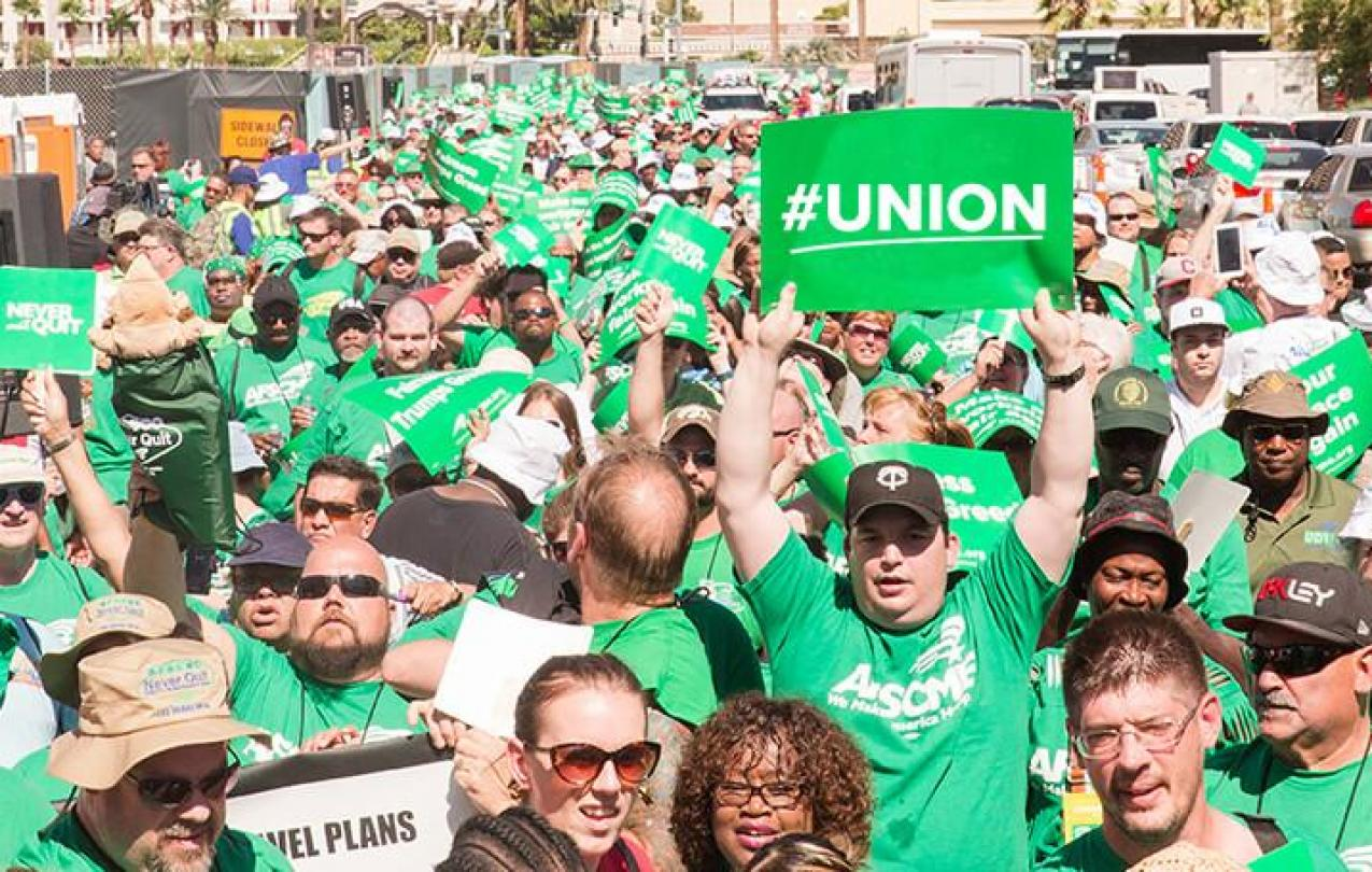 """Crowd of men and women in green AFSCME t-shirts, one is holding a green sign that reads, """"#UNION""""."""