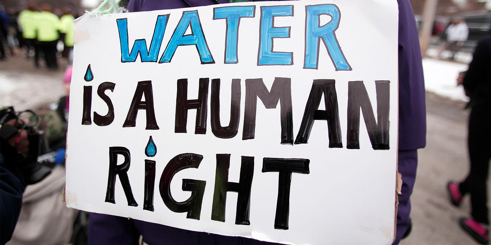"Image of a protest poster with ""WATER IS A HUMAN RIGHT"" written in bold letters."